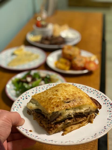 Hand holding plate of moussaka