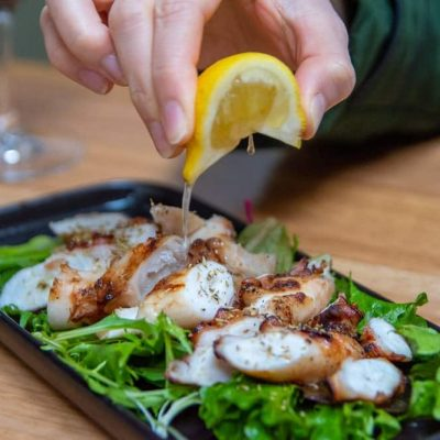 hand squeezing lemon over char grilled octopus on bed of salad